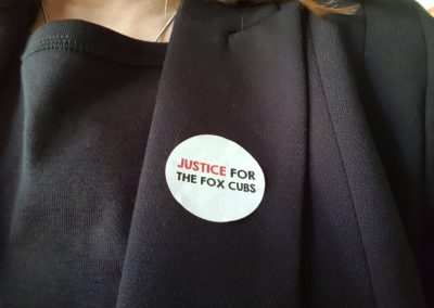 Jane Smith wearing a 'Justice for the Fox Cubs' badge, 2018